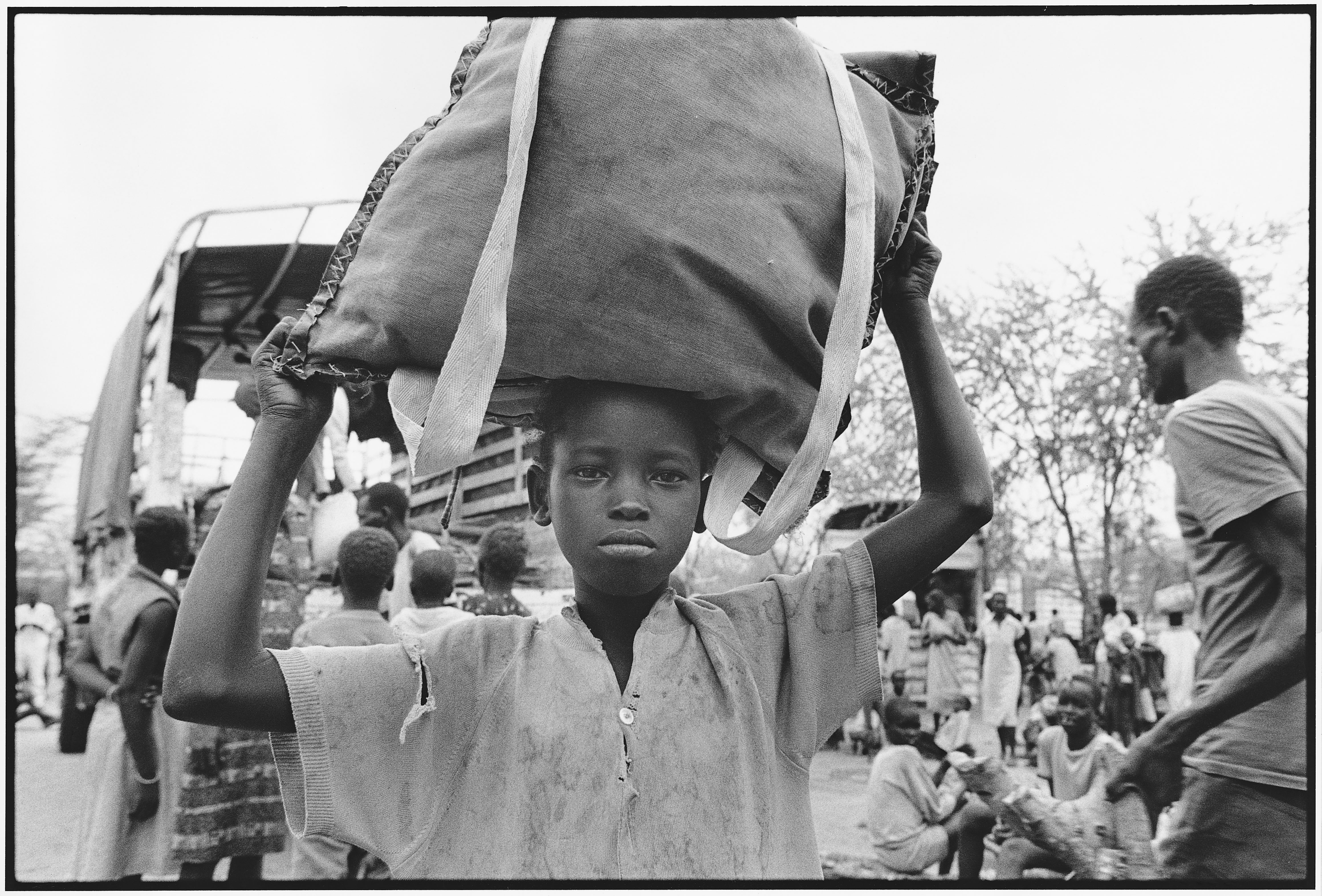 """Credit: UNHCR/B.Press Caption: A young Dinka boy arriving in Kenya in 1992. Determined to get an education, many of the """"Lost Boys"""" carried books with them across hundreds of miles of desert."""